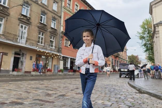 Niña pequeña caminando con un paraguas en una calle de la ciudad