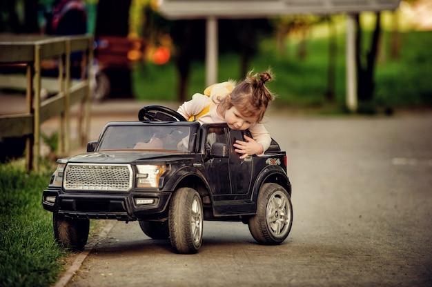 Niña pequeña conduciendo un coche de radiocontrol cabriolet negro de juguete grande en la carretera en el parque en verano y mirando hacia abajo con fondo borroso