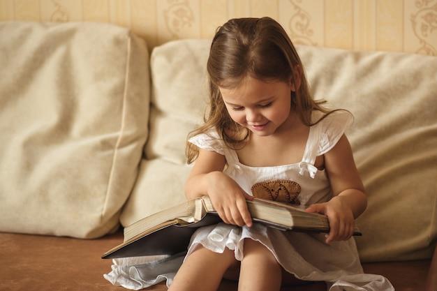 Niña pequeña está considerando un libro