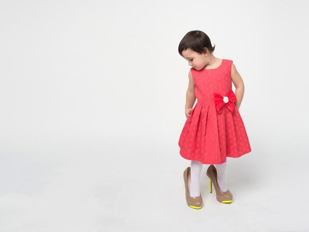 Niña pequeña divertida con cabello negro con un vestido rad está probando zapatos de tacones altos de su madre aislados