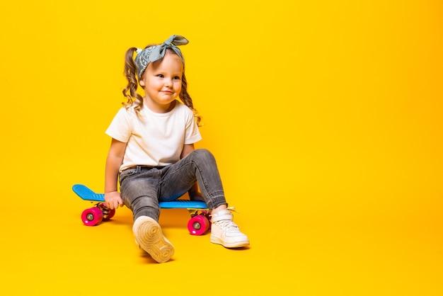 Niña pequeña con estilo en casual con patineta sobre pared amarilla.