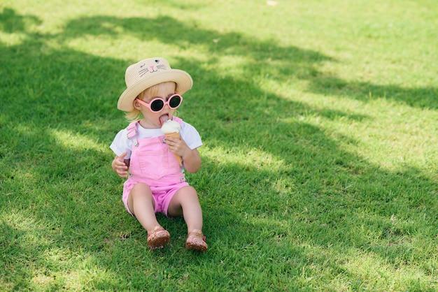 La niña pequeña feliz divertida que lleva el mono rosado del verano, el sombrero y las gafas de sol rosadas se sienta en un césped verde come el helado blanco de vainilla en un jardín soleado.