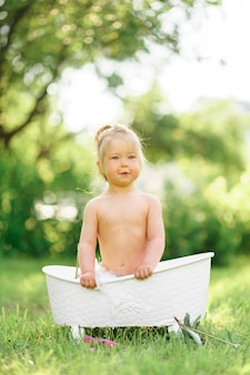 Niña pequeña feliz toma un baño de leche con pétalos. niña en un baño de leche. ramos de peonías rosas. bebé bañándose. higiene y cuidado de niños pequeños.