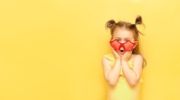 Niña pequeña en gafas de sol rojas de verano divertido expresión sorprendida mira a la cámara posando en la pared amarilla