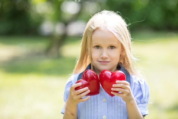 Niña pequeña y hermosa dulce y feliz con dos corazones rojos en sus manos