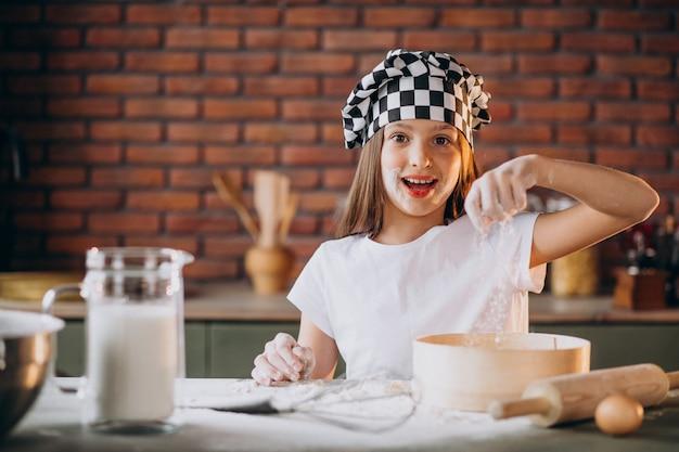Niña pequeña hornear pasteles en la cocina para el desayuno