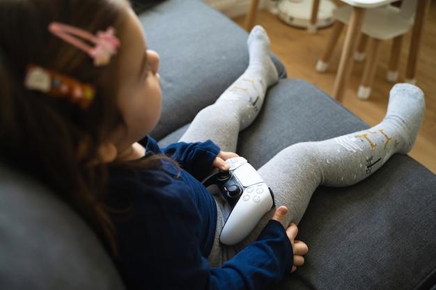 Niña pequeña jugando consola de videojuegos en casa en la sala de estar en el sofá. chico joven jugador.
