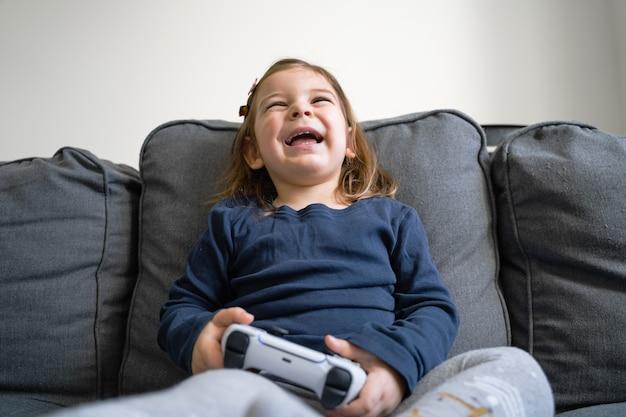 Niña pequeña jugando consola de videojuegos en casa en la sala de estar en el sofá