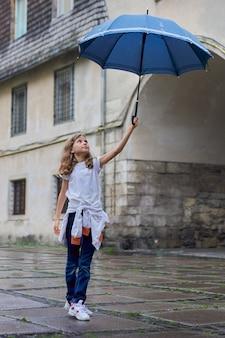 Niña pequeña bajo la lluvia con un paraguas, fondo turístico de la ciudad vieja