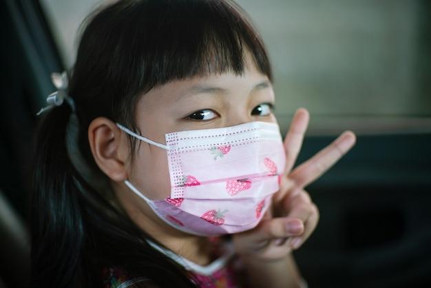Niña pequeña con mascarilla para prevenir el virus corona o covid-19 en el automóvil.