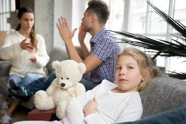 Niña pequeña molesta deprimida con padres argumentos o divorcio