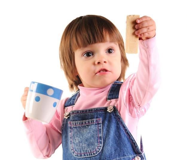 Niña pequeña en mono de jeans sosteniendo oblea y taza blanca en manos sobre fondo blanco en estudio fotográfico