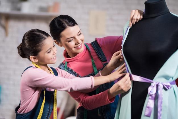 Una niña pequeña y una mujer adulta probándose ropa.