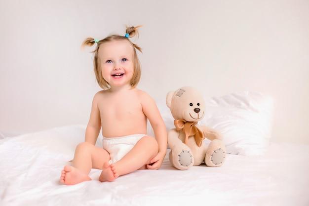 Niña pequeña en pañales se sienta con oso de juguete en la cama en su casa