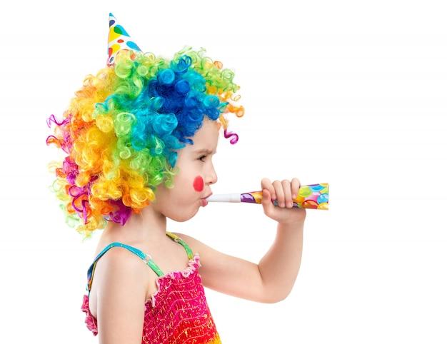 Niña pequeña en peluca de payaso con soplador de fiesta