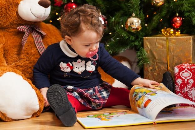 Niña pequeña que lee cuentos de hadas cerca del árbol de navidad.