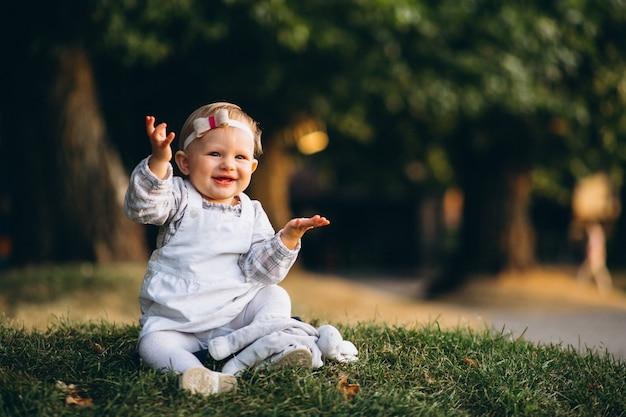 Niña pequeña que se sienta en hierba en parque