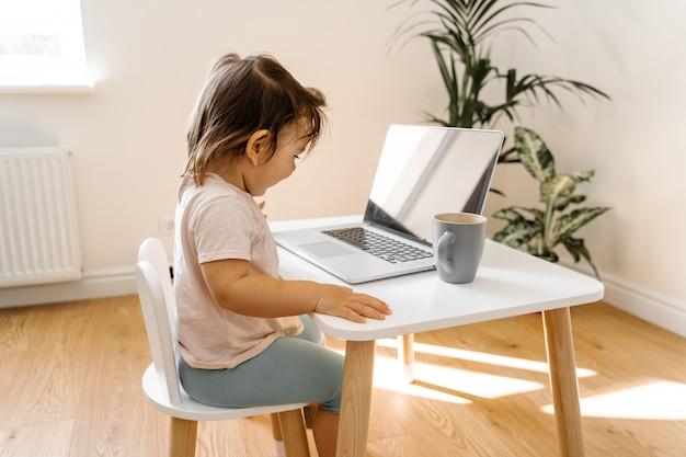 Niña pequeña que usa la computadora portátil en su tabla. vista superior. educación en línea
