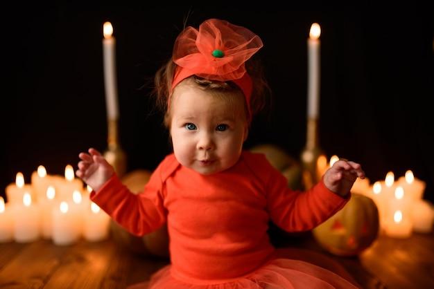 Niña pequeña se sienta con calabazas jack y velas