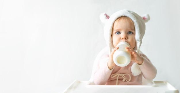 La niña pequeña en un sombrero mullido caliente bebe leche de una botella mientras está sentado. fondo gris