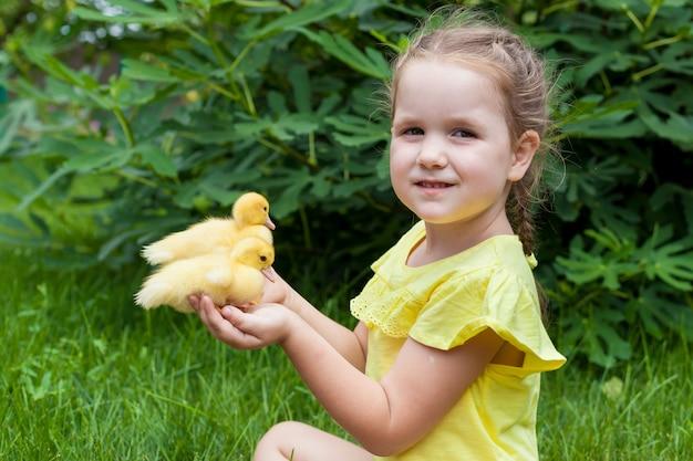 Una niña pequeña sostiene un patito en sus manos. naturaleza. pequeño granjero soleado dia de verano