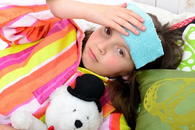 Una niña pequeña en su cama tiene dolor de cabeza.
