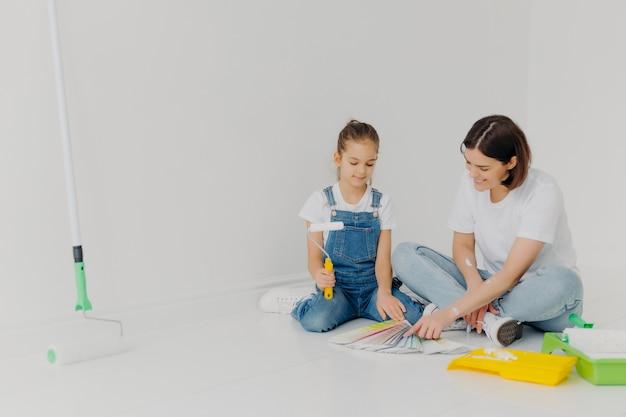 Niña pequeña y su madre se sientan en el piso