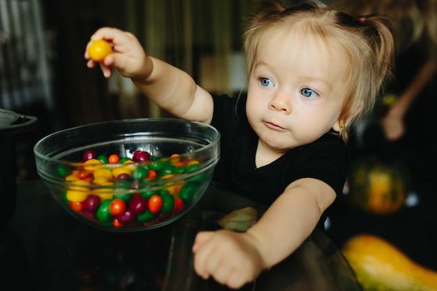 Niña pequeña sujetando un caramelo amarillo