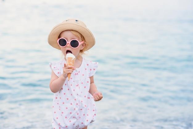 Niña pequeña vestida con ropa de verano y gafas de sol de color rosa se encuentra en la playa come con gran placer helado blanco. felices vacaciones de verano.