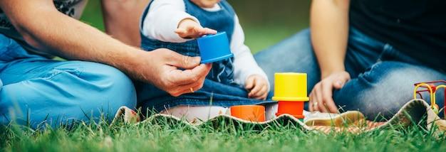 Niña pequeña en vestido de jeans jugando con sus padres