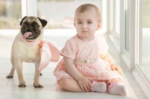 Niña pequeña con un vestido rosa junto a un cachorro pug