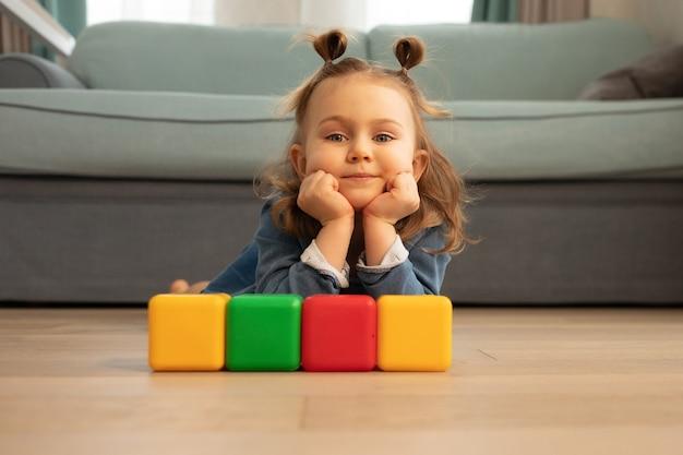 Una niña pequeña yace en el suelo con cubos de colores.