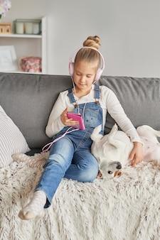Niña y perro acostado en el sofá con auriculares, escuchando música con su teléfono inteligente