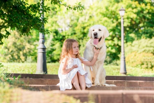 Niña con un perro blanco grande en el parque. una hermosa niña de 5 años vestida de blanco abraza a su perro favorito durante un paseo de verano.