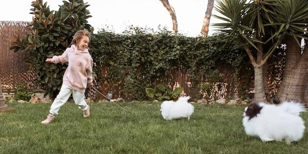 Niña y perros corriendo y jugando.