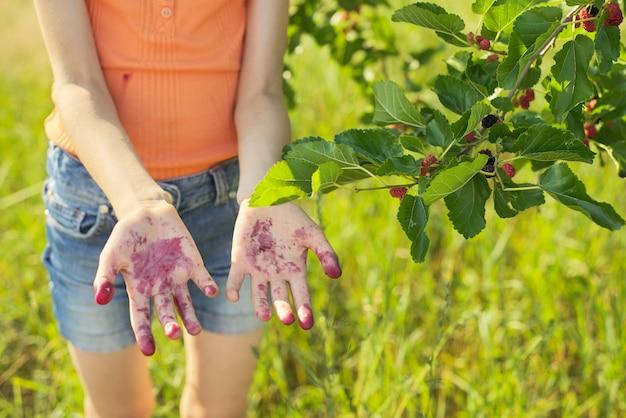 Niña de pie bajo un árbol con moras maduras con manos de bayas sucias