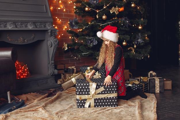 Niña de pie cerca del árbol de navidad con presente