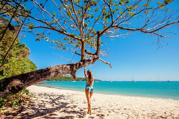 Niña de pie cerca del árbol en la playa con agua clara