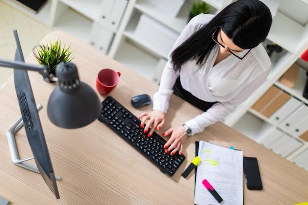 Una niña está de pie cerca de la mesa y escribiendo texto en el teclado. al lado de la niña se encuentran documentos y un marcador.