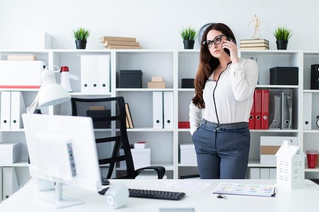 Una niña de pie cerca de la mesa y hablando por teléfono.