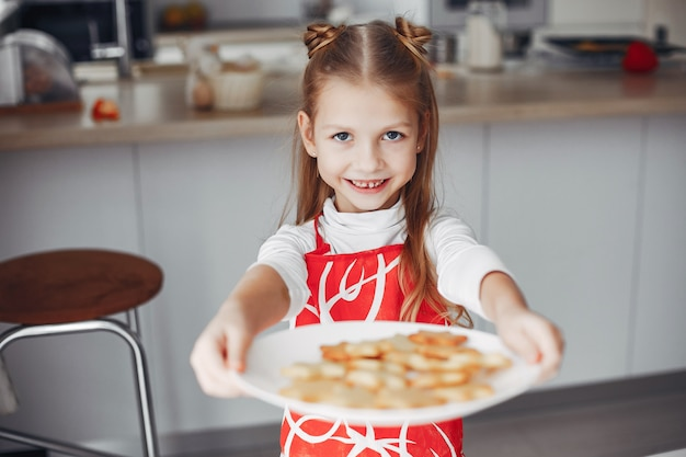 Niña de pie en una cocina con galletas