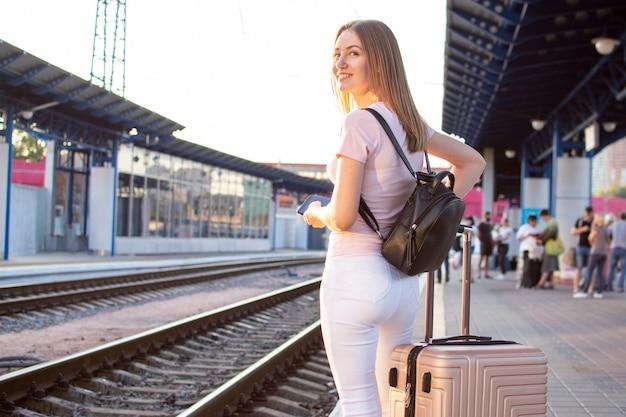 Niña de pie con el equipaje en la estación