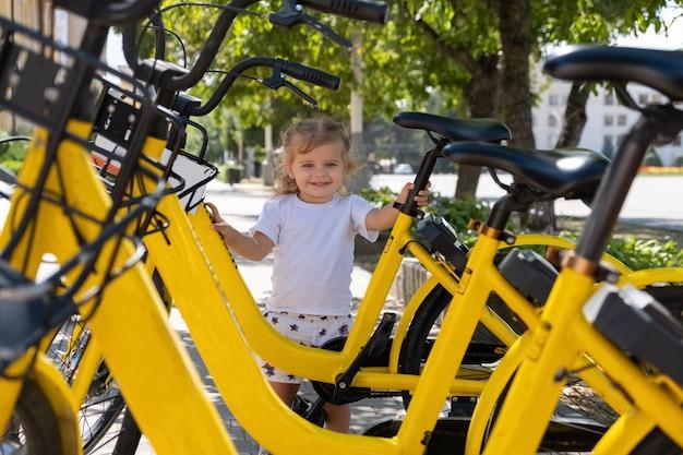 Niña está de pie junto a la bicicleta para alquilar en el estacionamiento de la ciudad