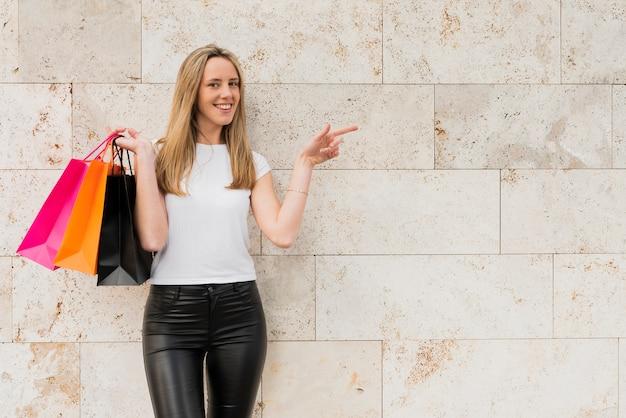 Niña de pie junto a la pared con bolsas de compras