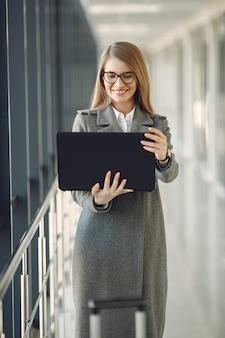 Niña de pie en la oficina con una computadora portátil