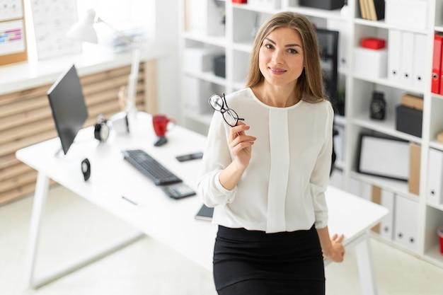Una niña está de pie, recostada sobre una mesa en la oficina y con gafas en la mano.