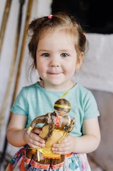 La niña está de pie y sostiene una muñeca.