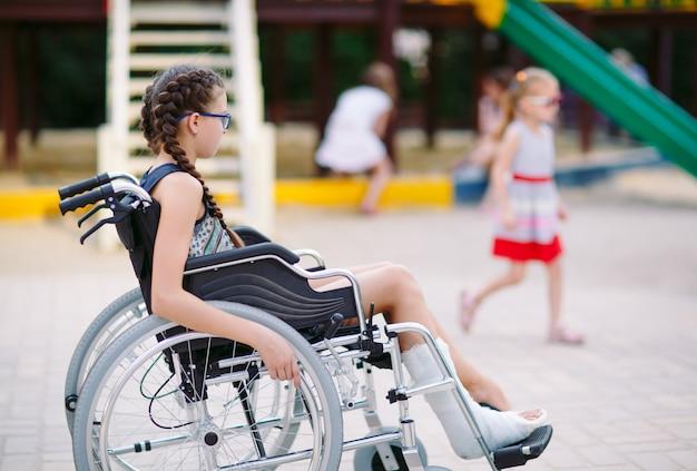 Una niña con una pierna rota se sienta en una silla de ruedas frente al patio de recreo.