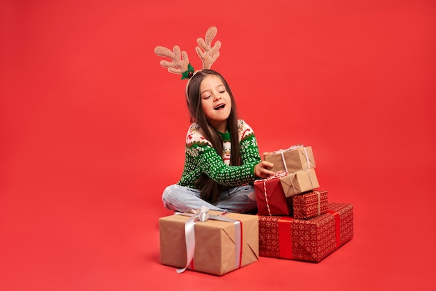 Niña y una pila de regalos de navidad