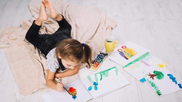 Niña pintando con acuarelas sobre papel cerca de dibuja y acostada en el piso